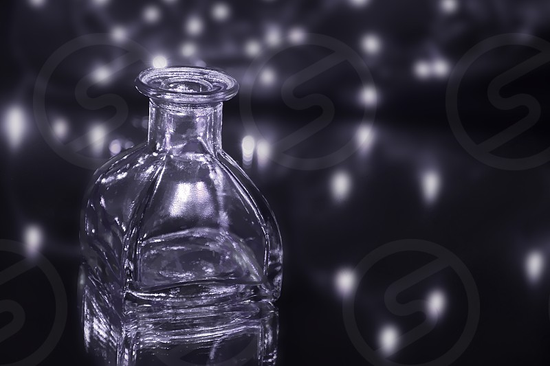 Galaxy away-still life abstractempty bottle on reflecting surface with lights in background. photo
