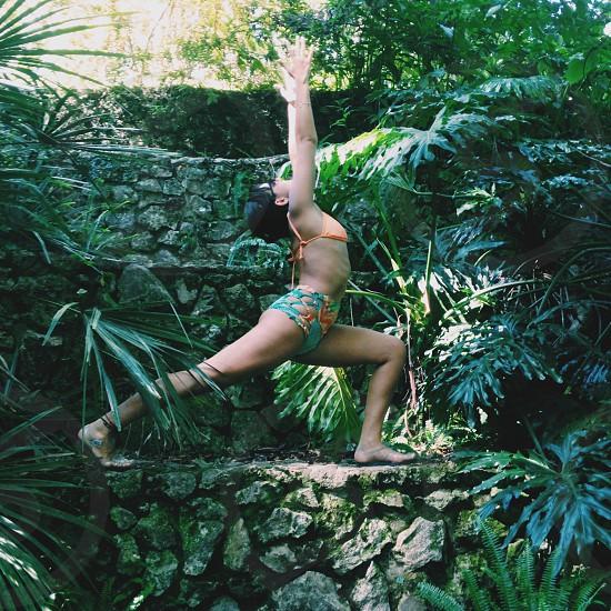 woman wearing orange bikini top doing yoga photo