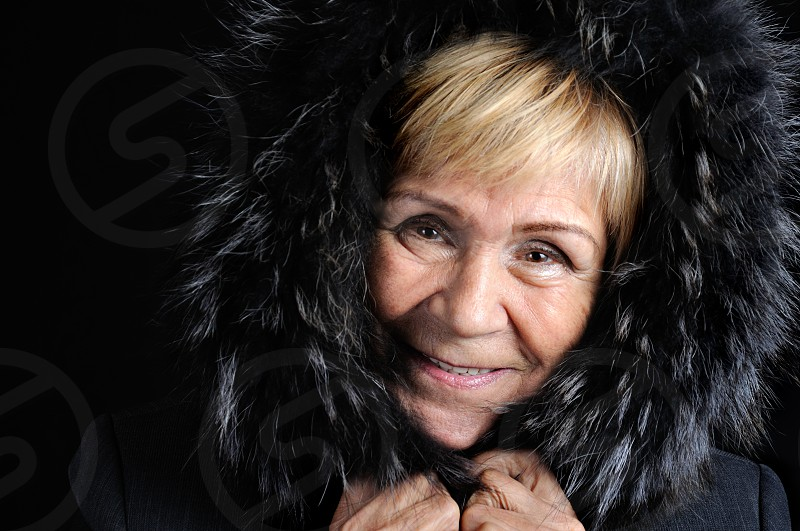 Portrait of an elderly woman wrapped in a fur hood on a dark background close-up photo