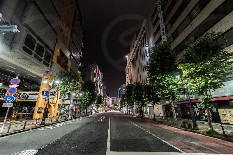 concrete road and high-rise buildings at nighttime photo