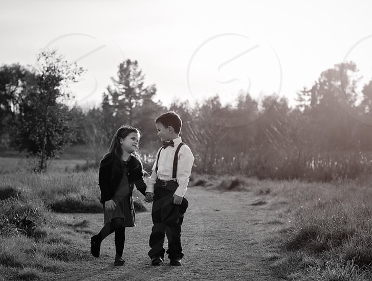 grayscale photography of boy and girl walking on brown pathway photo