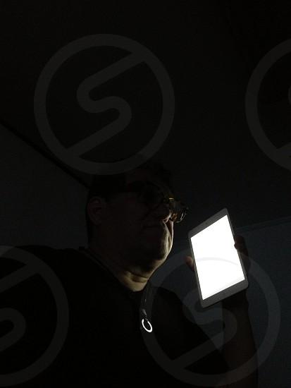 man with black tee and eye glasses holding ipad photo