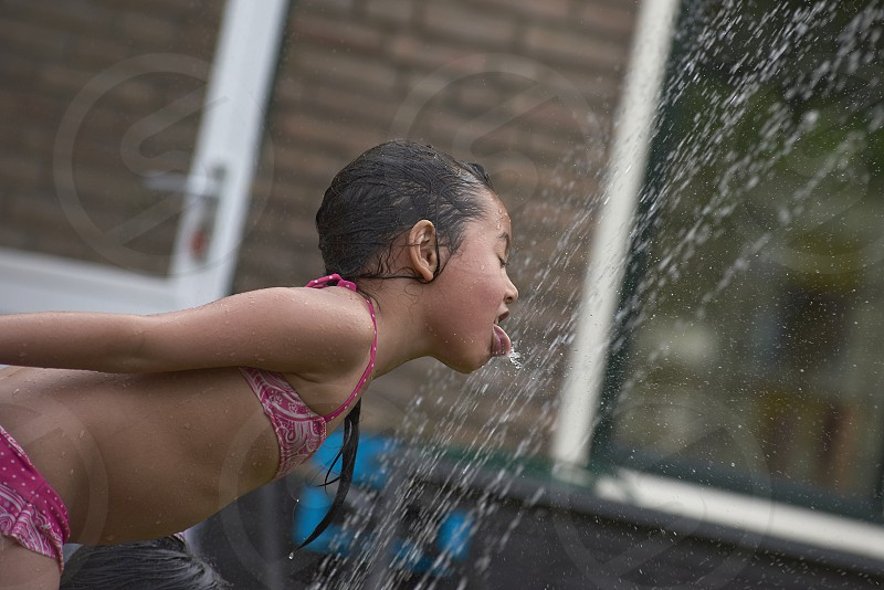 Cute young toddler Asian girl playing in a water sprinkler in the back garden in summer sunshine having lots of fun and laughing photo