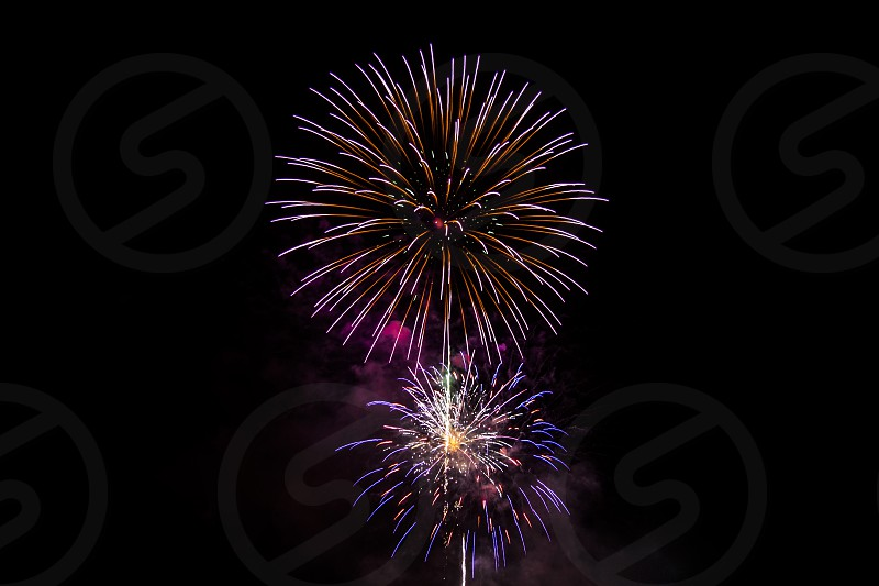 time lapse photography of purple white and brown fireworks on the sky during nighttime photo