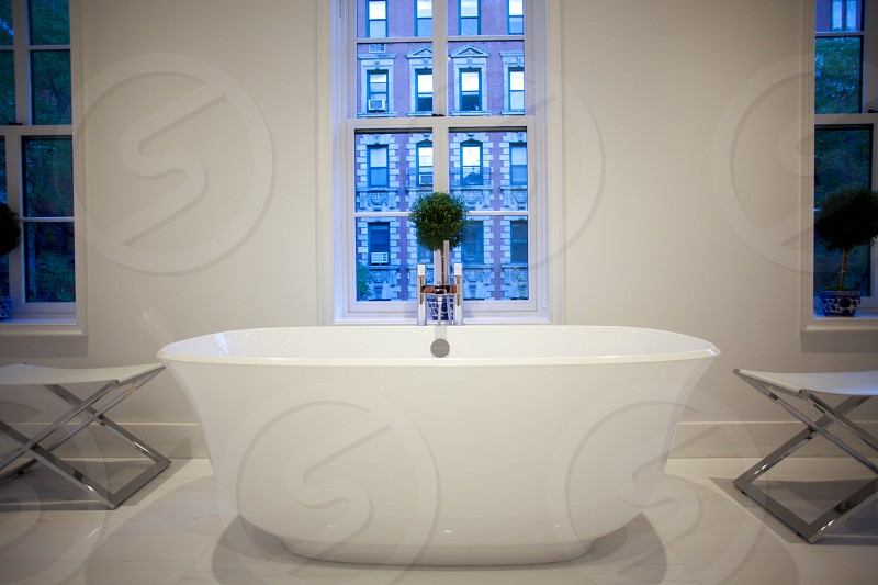 white ceramic bathtub near a stainless steel table and white frame window photo