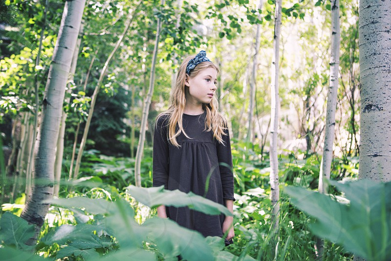 childkid girl 9 years old blonde long hair head band bow nature green aspens colorado mountains sweet innocent portrait natural lighting pretty little girl smile blue eyes brown shirt landscape trees wild hiking exploring playing outside looking to the side standing thinking dreaming photo