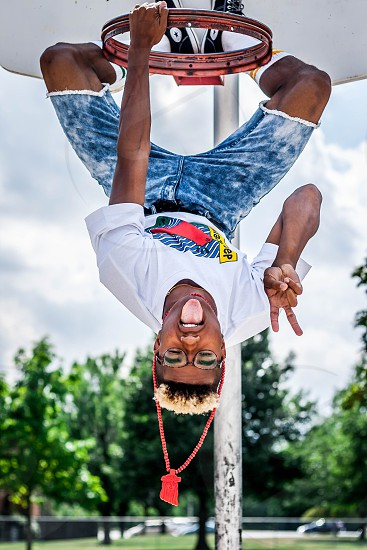 man in white t shirt hanging upside down and making peace sign photo