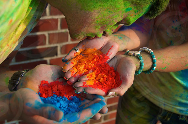 Powdered paint in cupped hands kissing photo