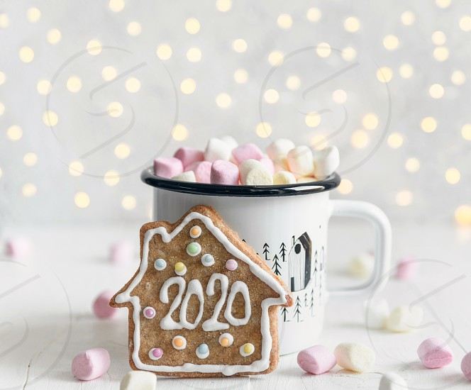 Gingerbread house with number 2020. Happy new year bokeh lights depth of focus mug hot beverage. photo