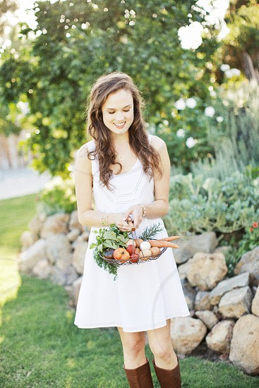woman with long brown hair smiling holding vegetable basket with white tank dress and brown boots near rocks photo