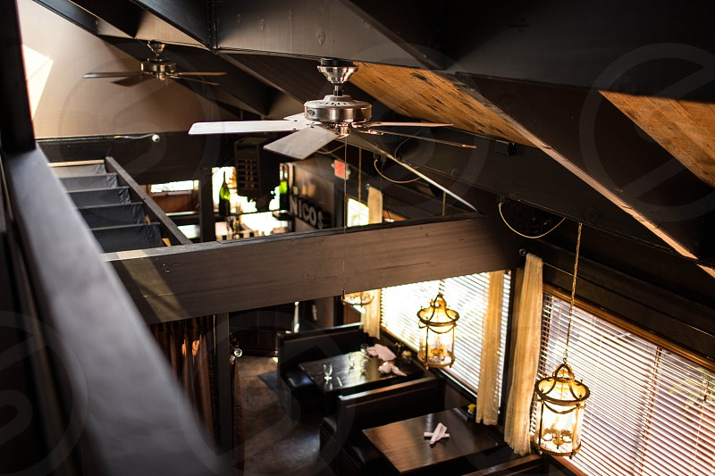 grey ceiling fan on brown and black wooden ceiling near hanging lantern inside room photo