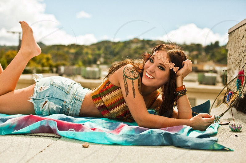 brunette woman with pink floral lace headband wearing green red brown and tan zig-zag striped halter crop top and blue denim shorts laying on pink and blue tie-dyed tower with dream catcher shoulder tattoo photo