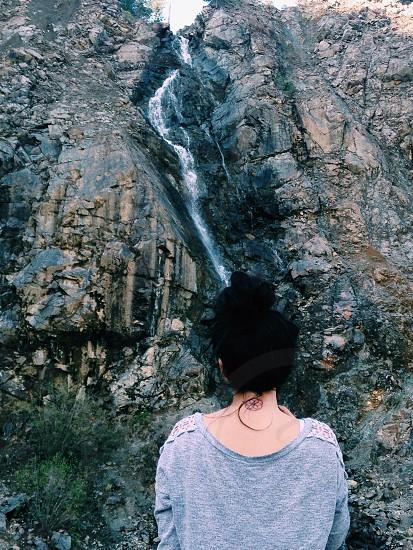 woman in grey shirt facing waterfalls photo