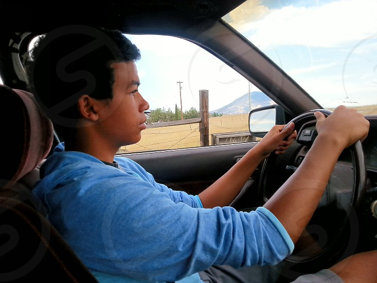 A teenager behind the wheel in preparation to take a drivers lisence test. photo