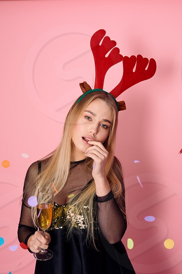 Pretty girl wear red horns hold a glass of champagne and pose to camera in pink background studio photo