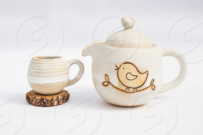 white teapot and ceramic stoneware cup with white background photo