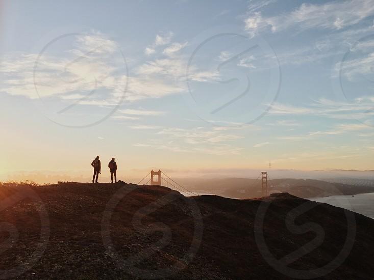 2 person on brown mad mountain near golden gate bridge during daytime photo