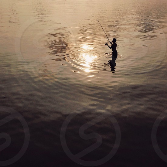 silhouette of man standing on calm body of water holding fishing rod photo
