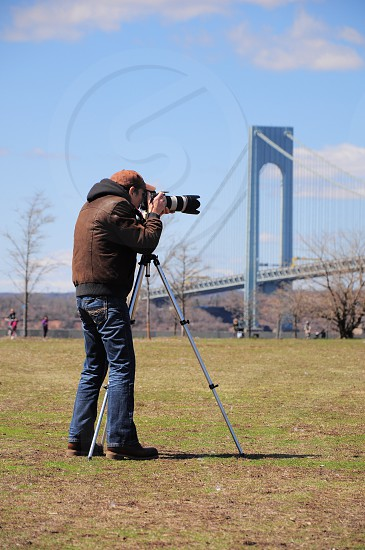 man in brown jacket with hood and blue denim jeans standing behind a grey and black dslr camera on tripod during daytime photo