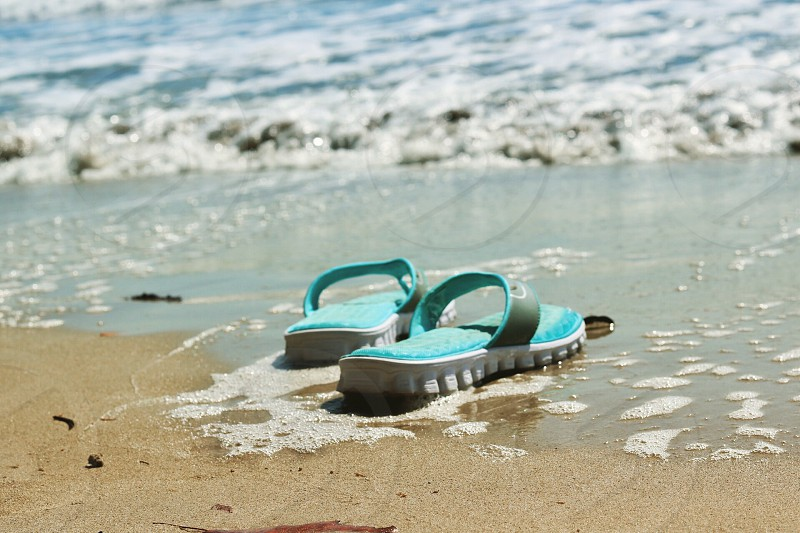 shallow focus photography of teal and white flippers on seashore during daytime photo