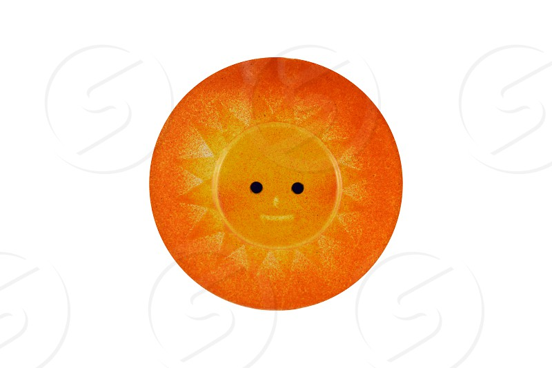 Orange sun decoration. Ceramic sun isolated on a white background. Round sun ornament photo