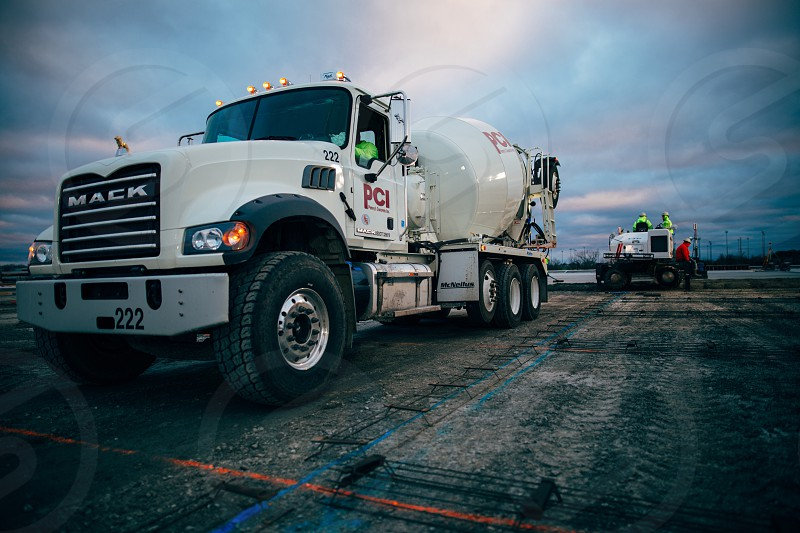 white mack cement truck on gray concrete floor under blue cloudy sky photo