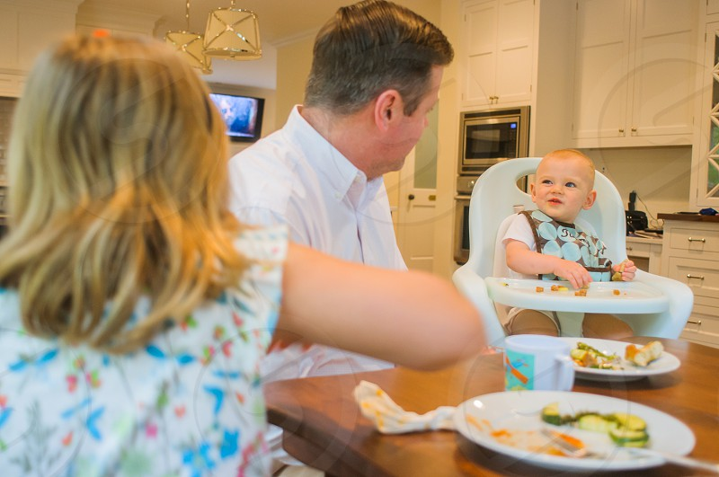 man in white dress shirt facing infant on white high chair by the table photo