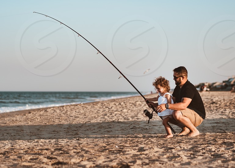 Coastal fishing; father and daughter beach  photo
