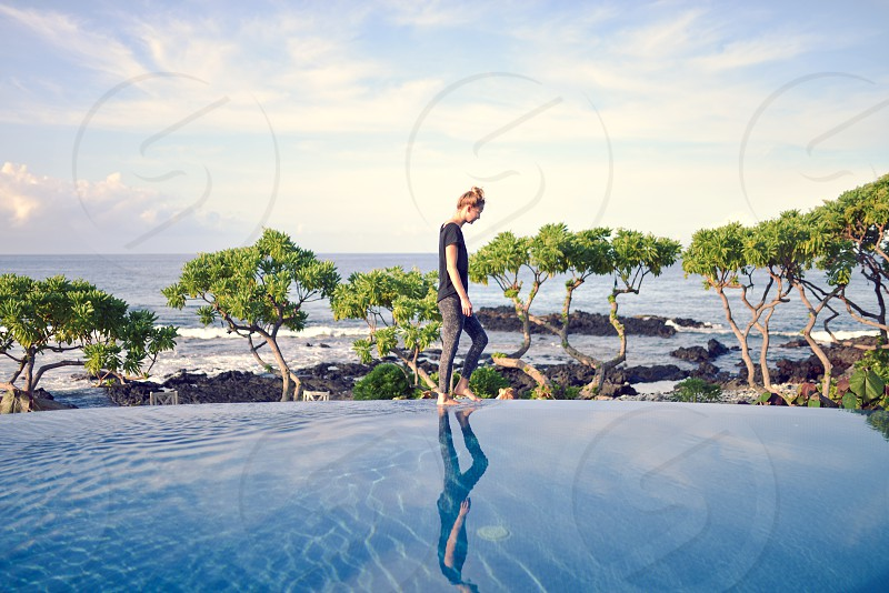 girl walking along infinity pool in tropical locale photo