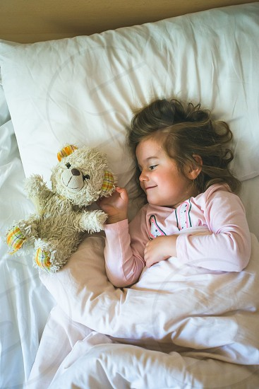 Little girl lying in a bed with teddy bear at the morning photo