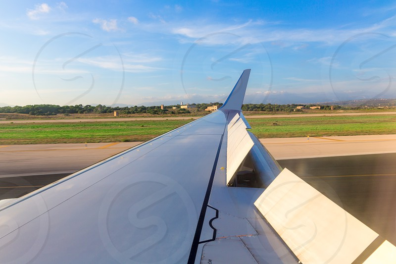 Aircraft airplane wing in landing process in blue sky day photo