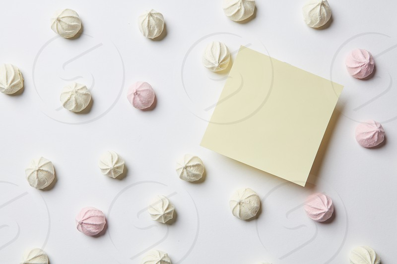Valentine's day concept. Stick represented among handmade sweet pink zephyr marshmallow over white background. Heart small candies of white and pink colors. photo