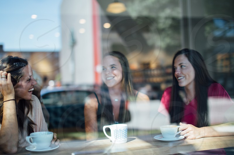 photo of 3 woman sitting with 3 ceramic teacup photo