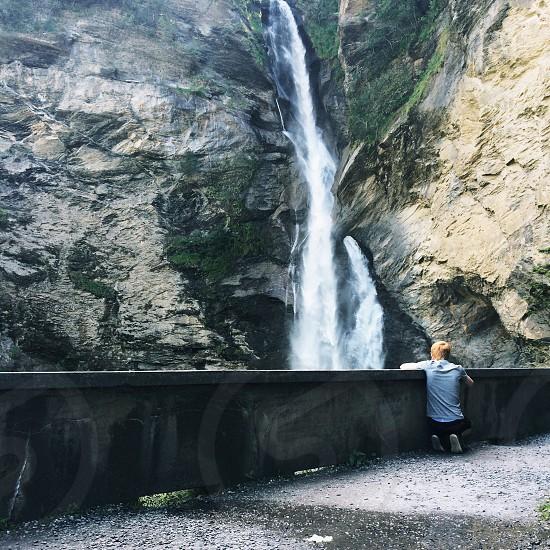 man sitting looking at the falls photo