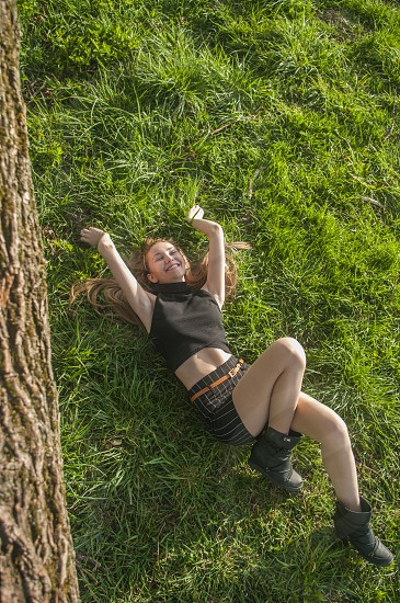 woman in black halter neck crop top and black skirt wearing black boots lying on green grass near tree during daytime photo