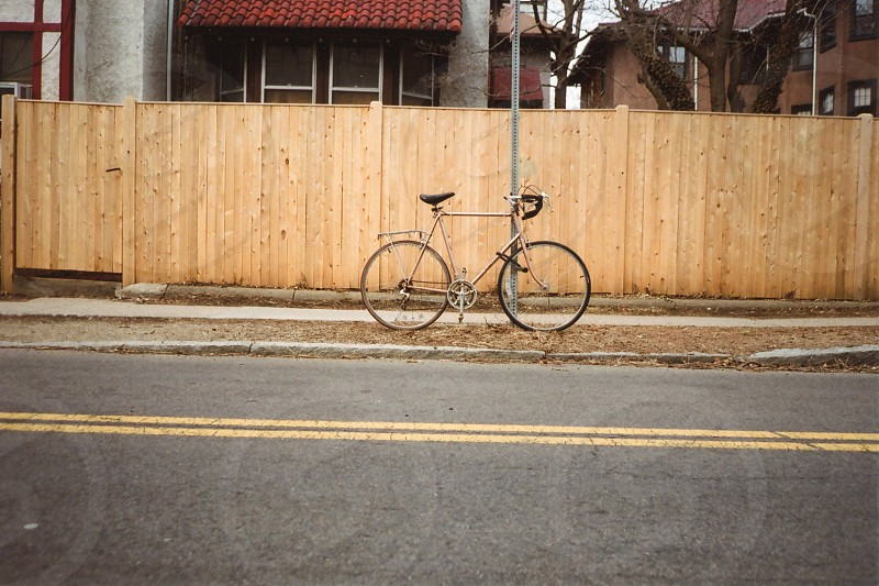 bicycle tied to a silver pole by a street and wooden fence photo