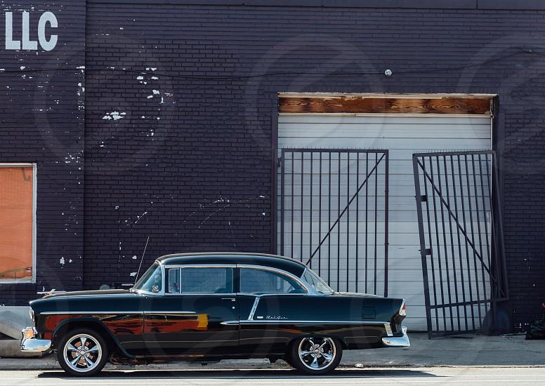 black vintage chevrolet bel air coupe next to black brick building photo