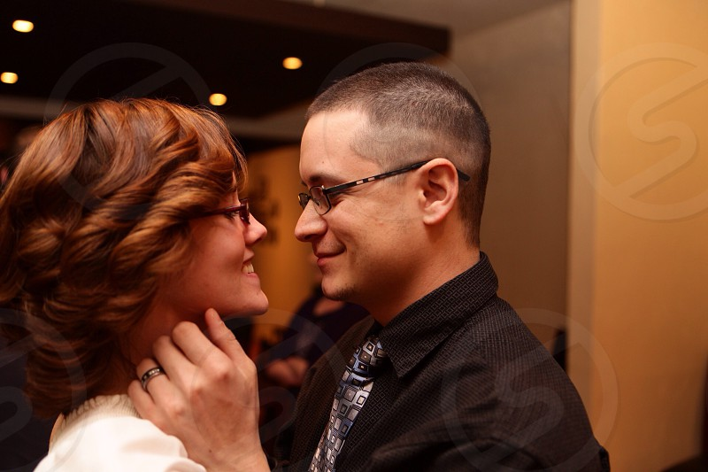 smiling brunet man and woman wearing eyeglasses facing each other photo