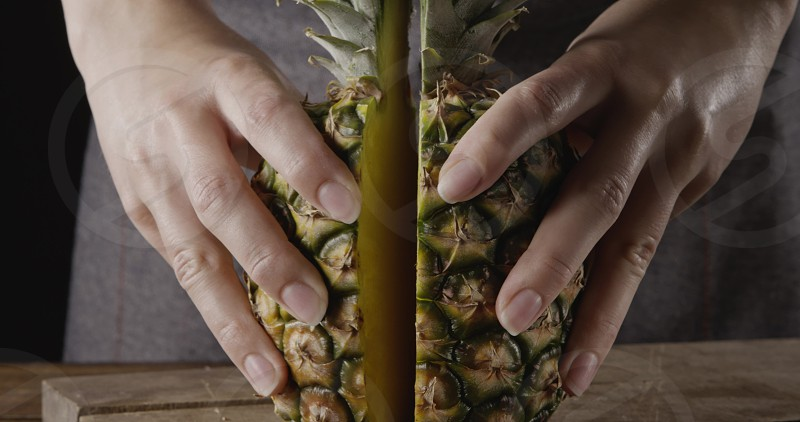 Chef's hands with fresh ripe natural organic exotic fruits cutting on a wooden table . Close up view. Concept of vegetarian diet eating. photo