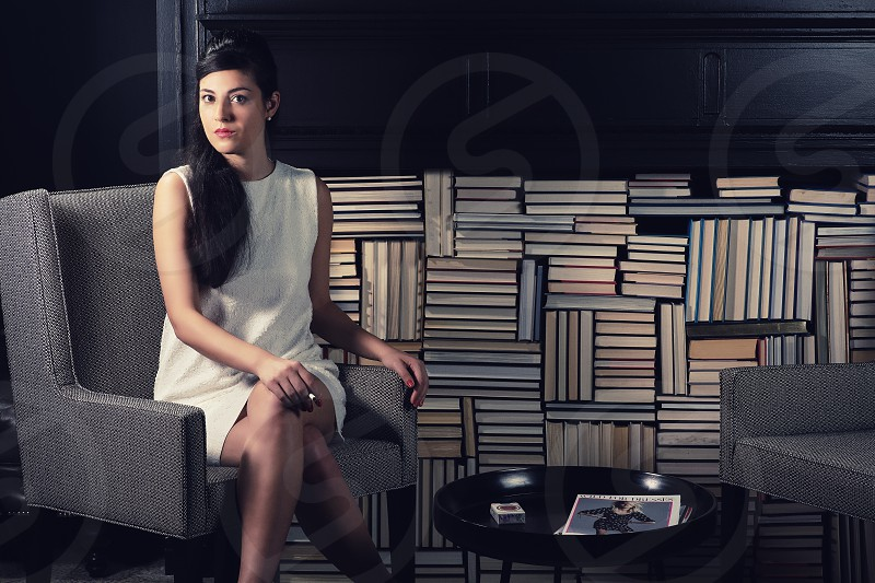 woman in white sheath dress and long black hair near stacked books seated in gray chair photo