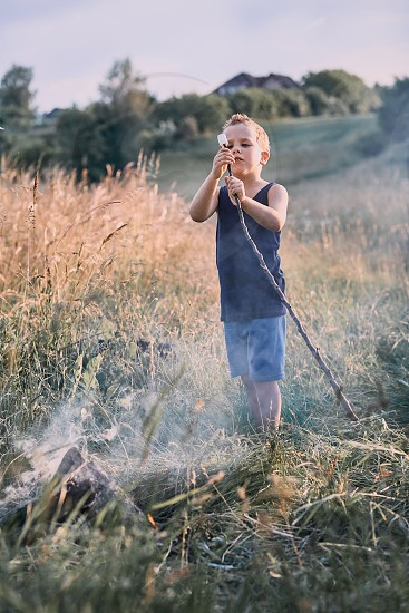 Little boy roasting marshmallow over a campfire on a meadow. Candid people real moments authentic situations photo