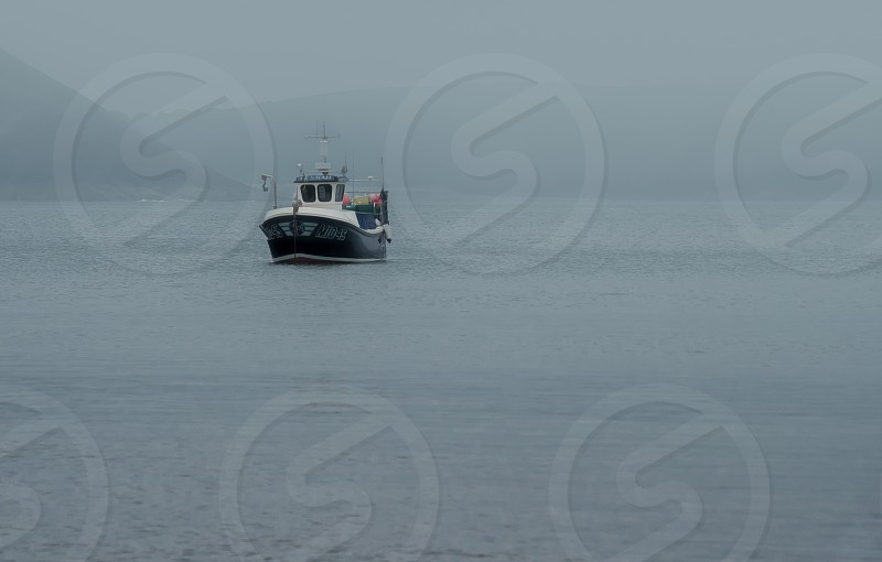 A fishing boat emerging through the fog off the coast at Freshwater East Pembrokeshire Wales. photo
