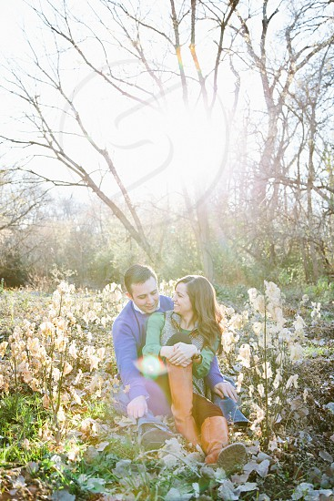 man and woman sitting on flower garden photo