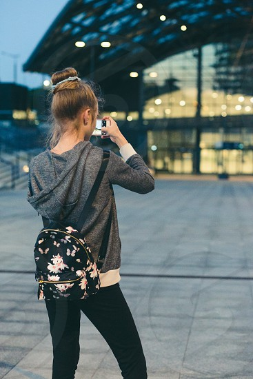 Young woman taking photos using a smartphone in the city at night photo