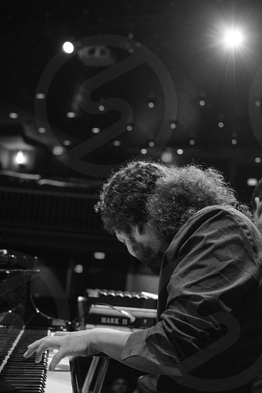 grayscale photo of man in long-sleeved top playing piano photo
