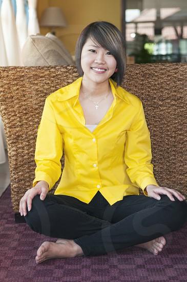 Happy female millennial sitting on carpet floor in living room photo