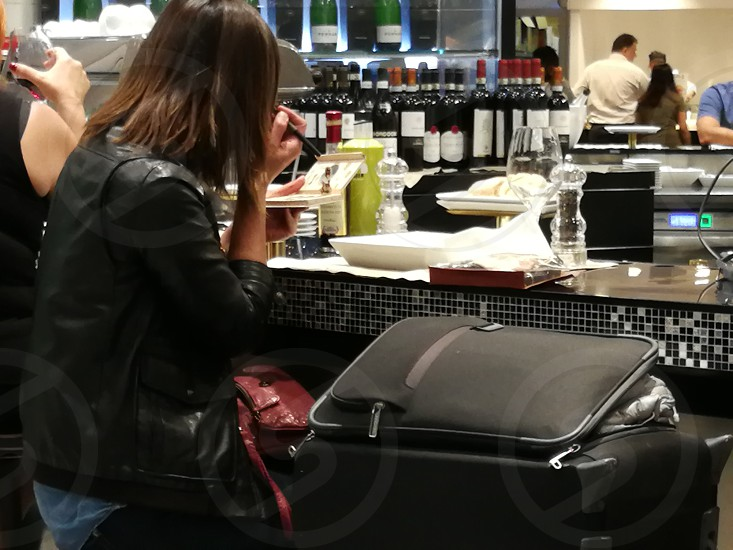 woman in black leather jacket with red bag on her lap and black softside luggage on side photo
