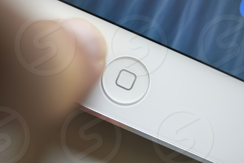Close up of hand pressing home button on a mobile device photo