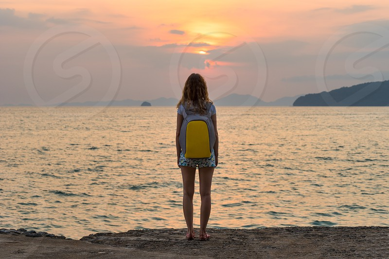 One young female tourist traveler with a backpack stands and looks at the sea at the beautiful sunset and seascape. Full rear view. photo