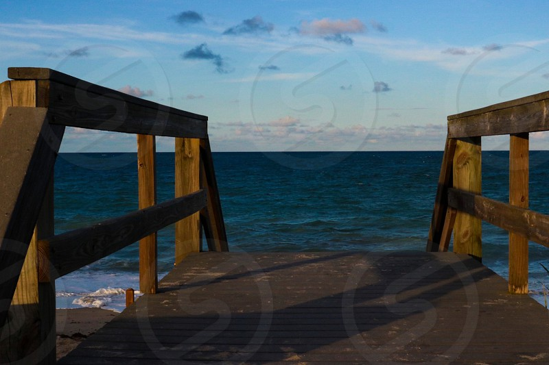 Vero beach south Florida Florida water ocean Boardwalk pier cloudscape sunset clouds over water Atlantic Ocean east coast wood sand sun  photo